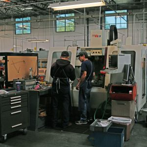 Two operators consulting on a job being run on one of the Bridgeport CNC mills.